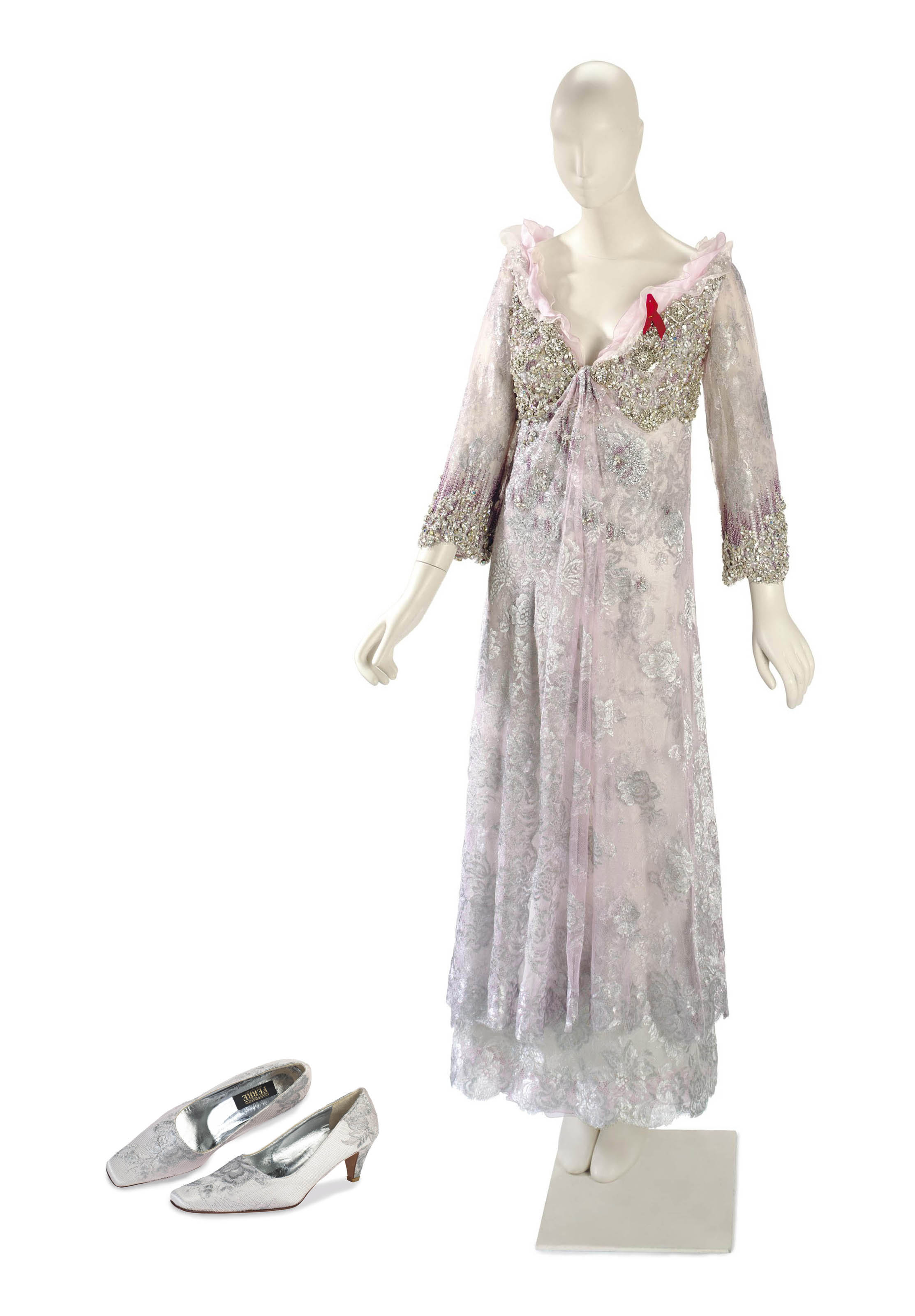 AN EVENING GOWN OF LILAC AND SILVER LACE WITH A RED 'AIDS' RIBBON AND MATCHING SHOES
