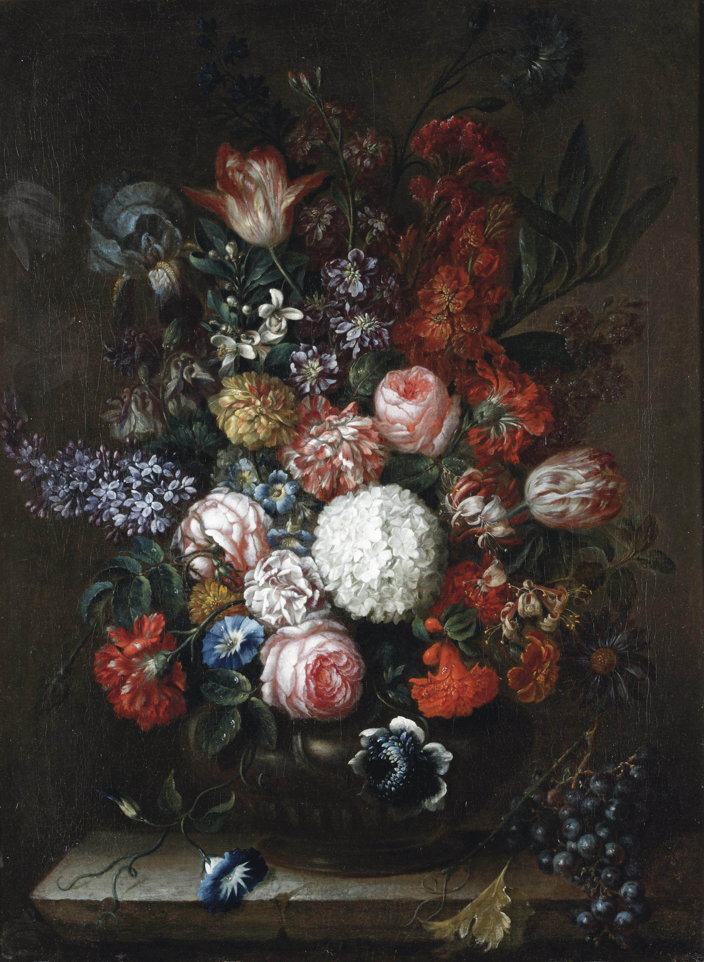Roses, carnations, honeysuckle, wisteria and other flowers with blue grapes, all on a stone ledge