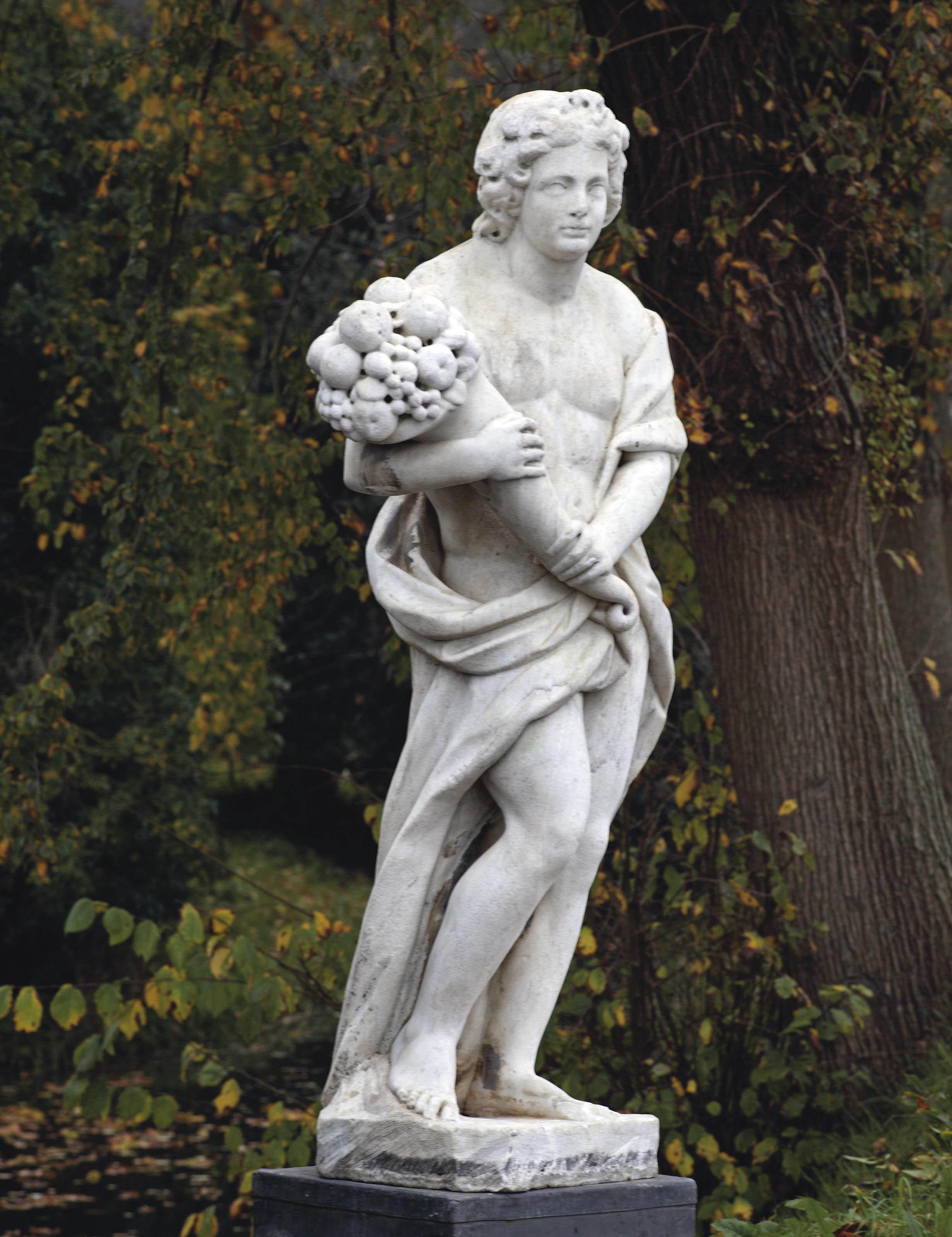 A carved carrara marble figure holding a cornucopia