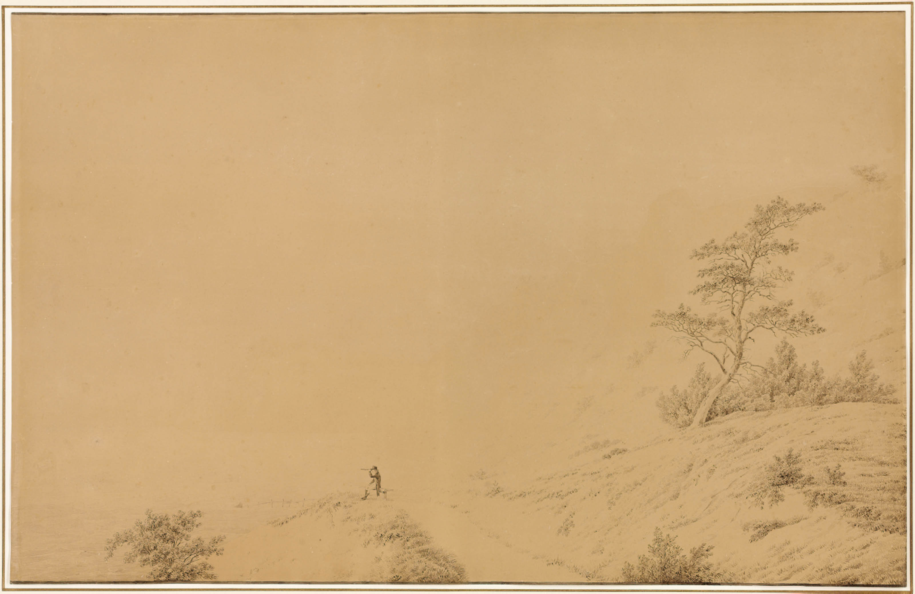 White chalk cliffs on the island of Möen, with a seated man looking at the sea with a telescope