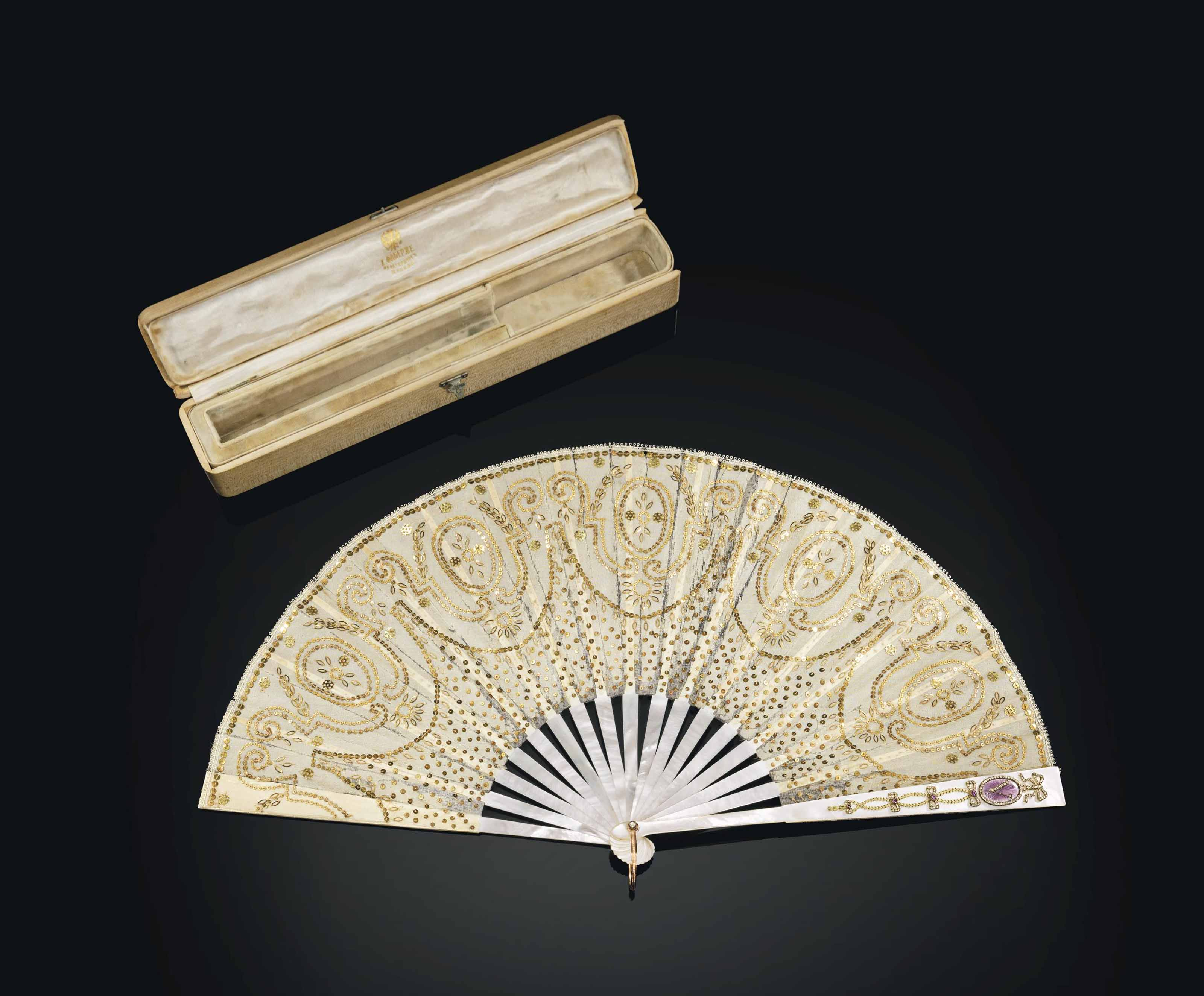 A JEWELLED TWO-COLOUR GOLD-MOUNTED MOTHER-OF-PEARL AND GUILLOCHÉ ENAMEL FAN