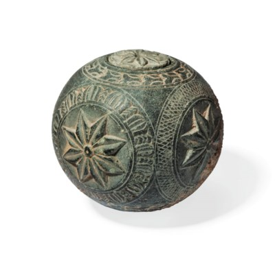 A CARVED GREY SCHIST SPHERICAL