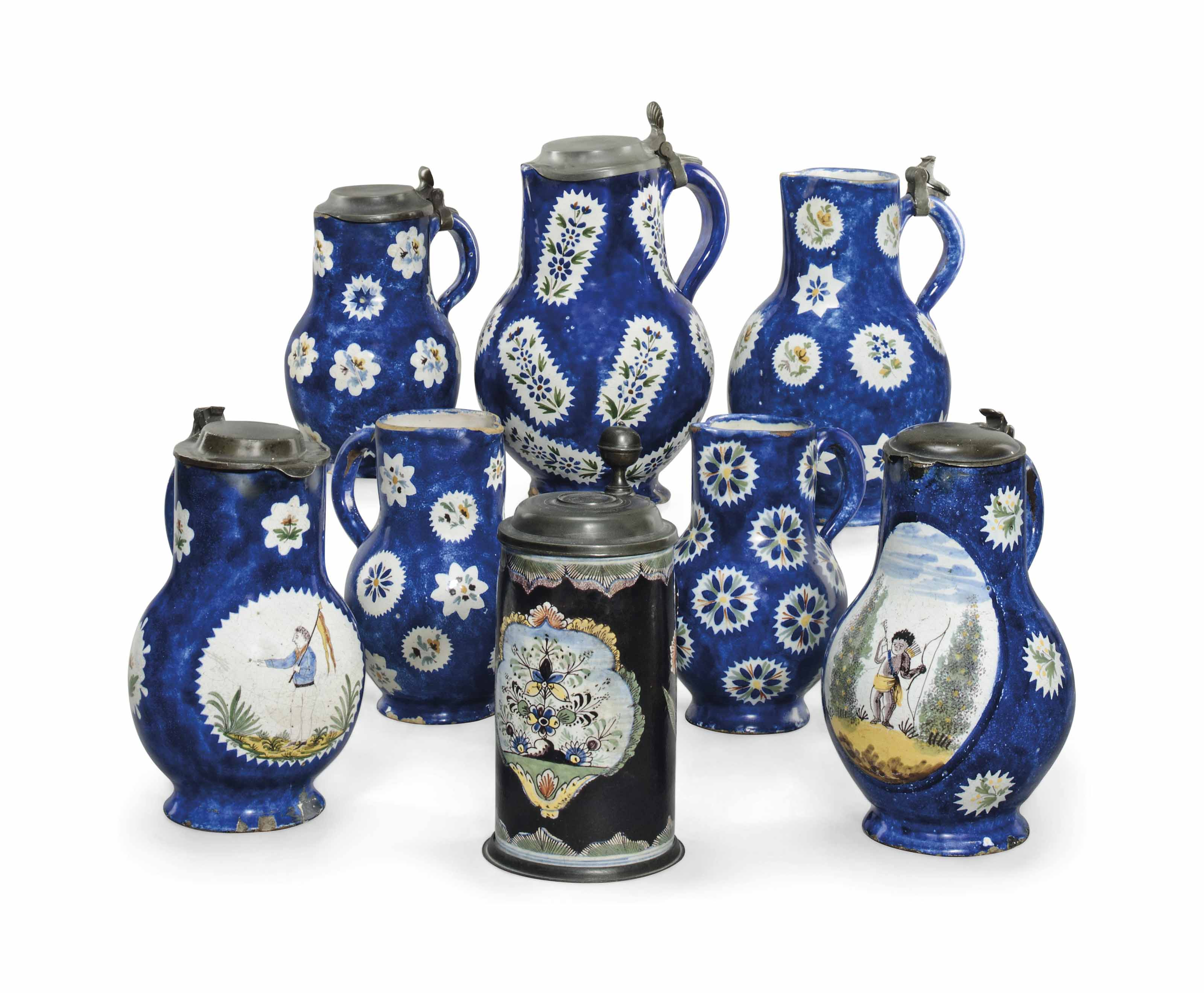 SEVEN BRUSSELS FAIENCE BLUE-GROUND JUGS AND A GERMAN FAYENCE BLACK-GROUND TANKARD