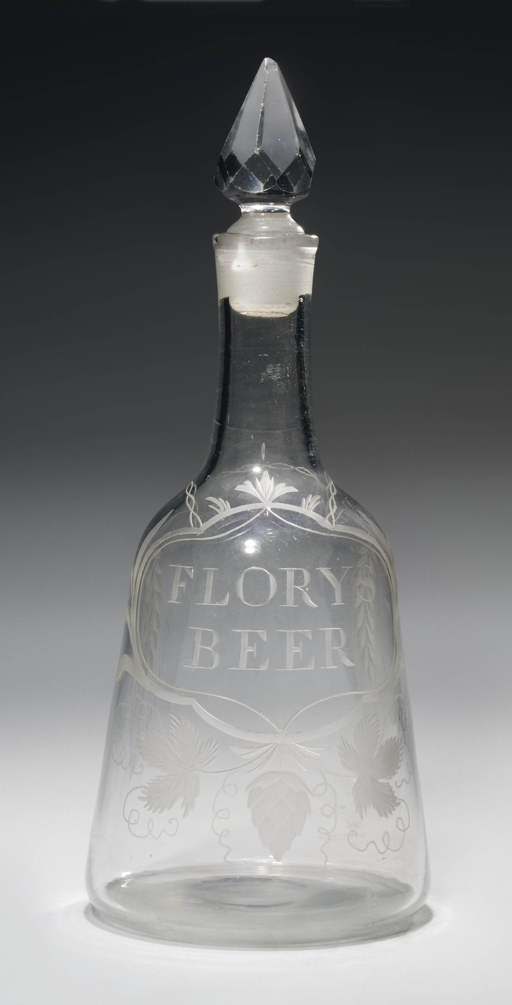 AN ENGRAVED GLASS ALE DECANTER