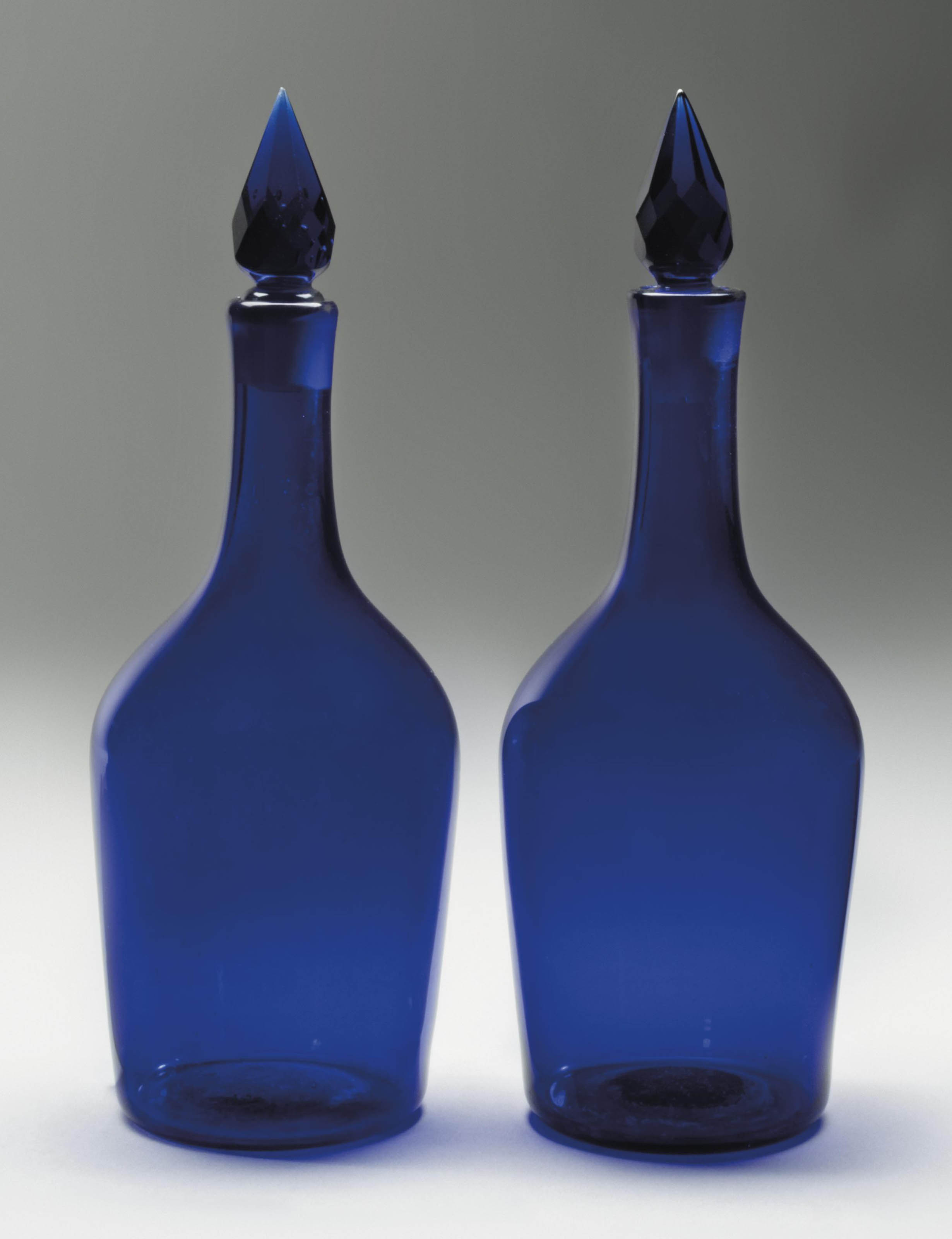 A PAIR OF BLUE GLASS CLUB-SHAPED DECANTERS AND STOPPERS