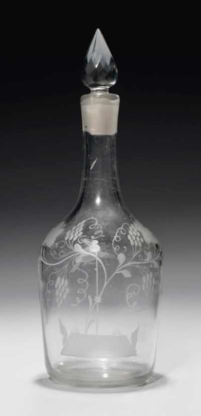AN ENGRAVED GLASS DECANTER AND