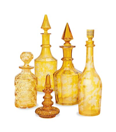 FOUR AMBER CUT-GLASS DECANTERS
