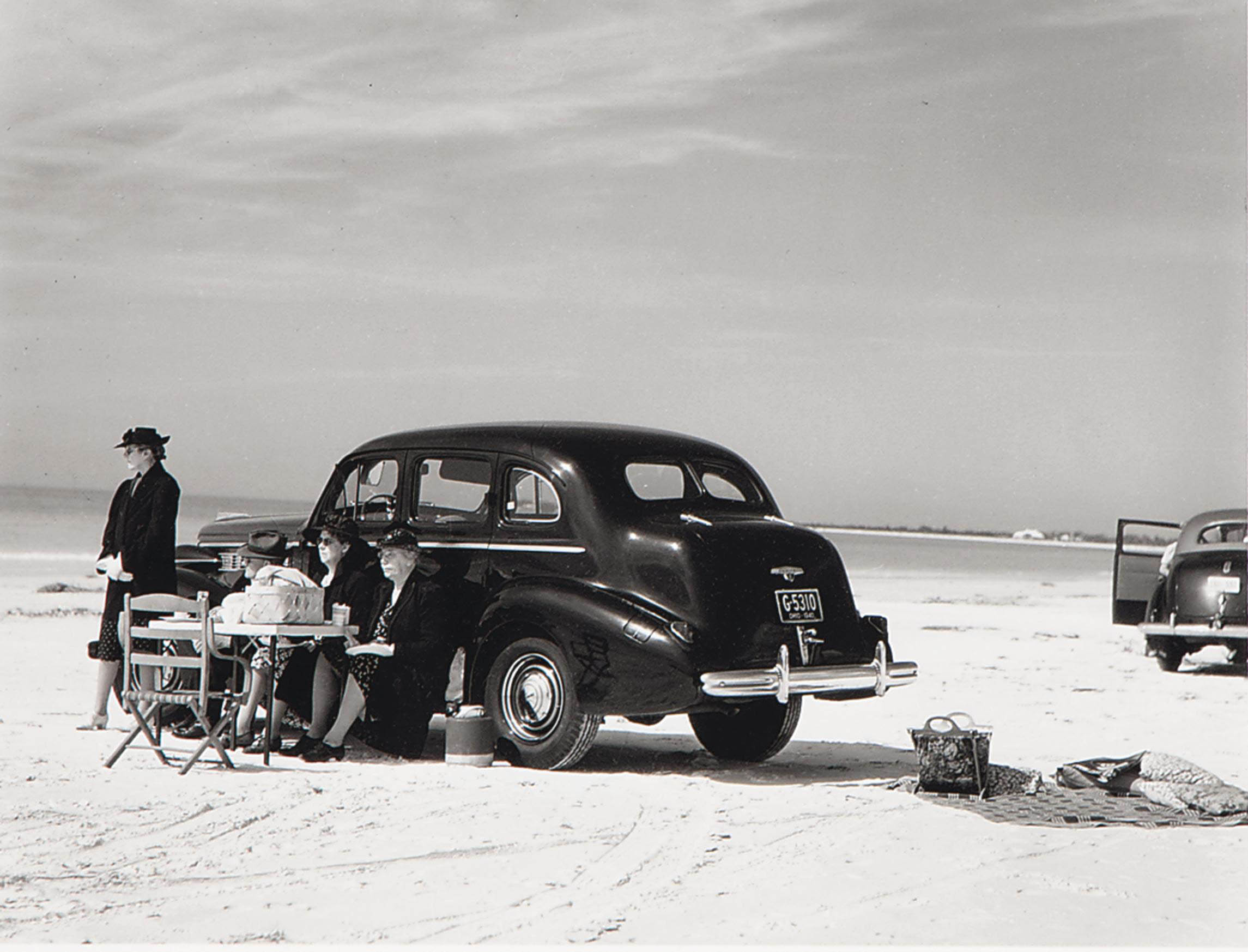 Winter tourists picnicking on running board of car, Sarasota, Florida, 1941