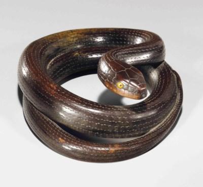 A carved wood model of a snake