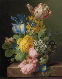 A vase of flowers with a bird's nest on a marble ledge
