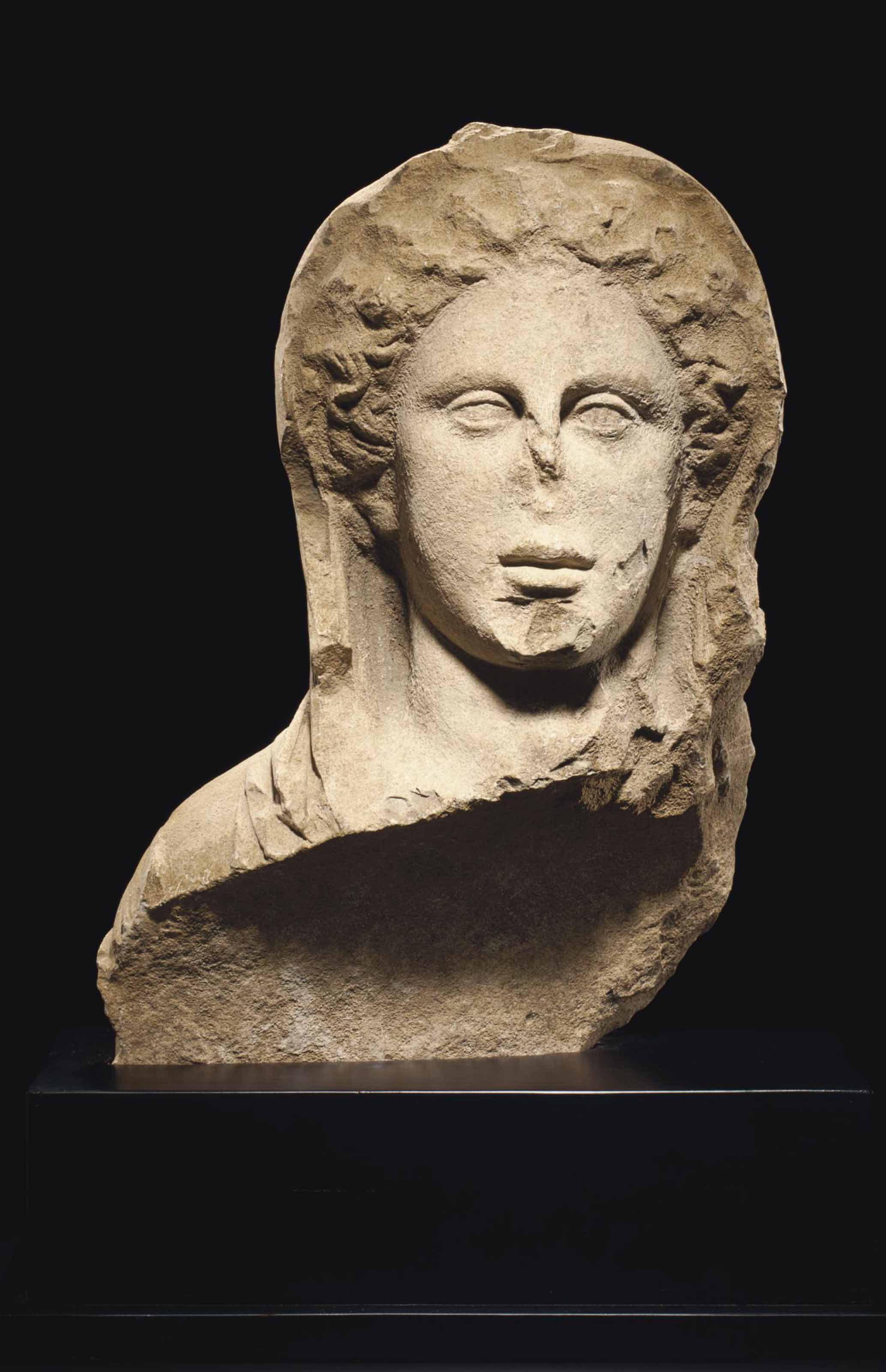 A GREEK LIMESTONE BUST OF A YO