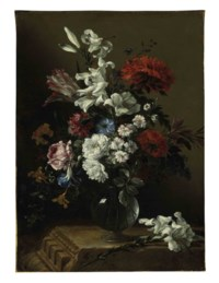 Lilies, roses, tulips, carnations, and other flowers in a glass vase on a classical architectural fragment