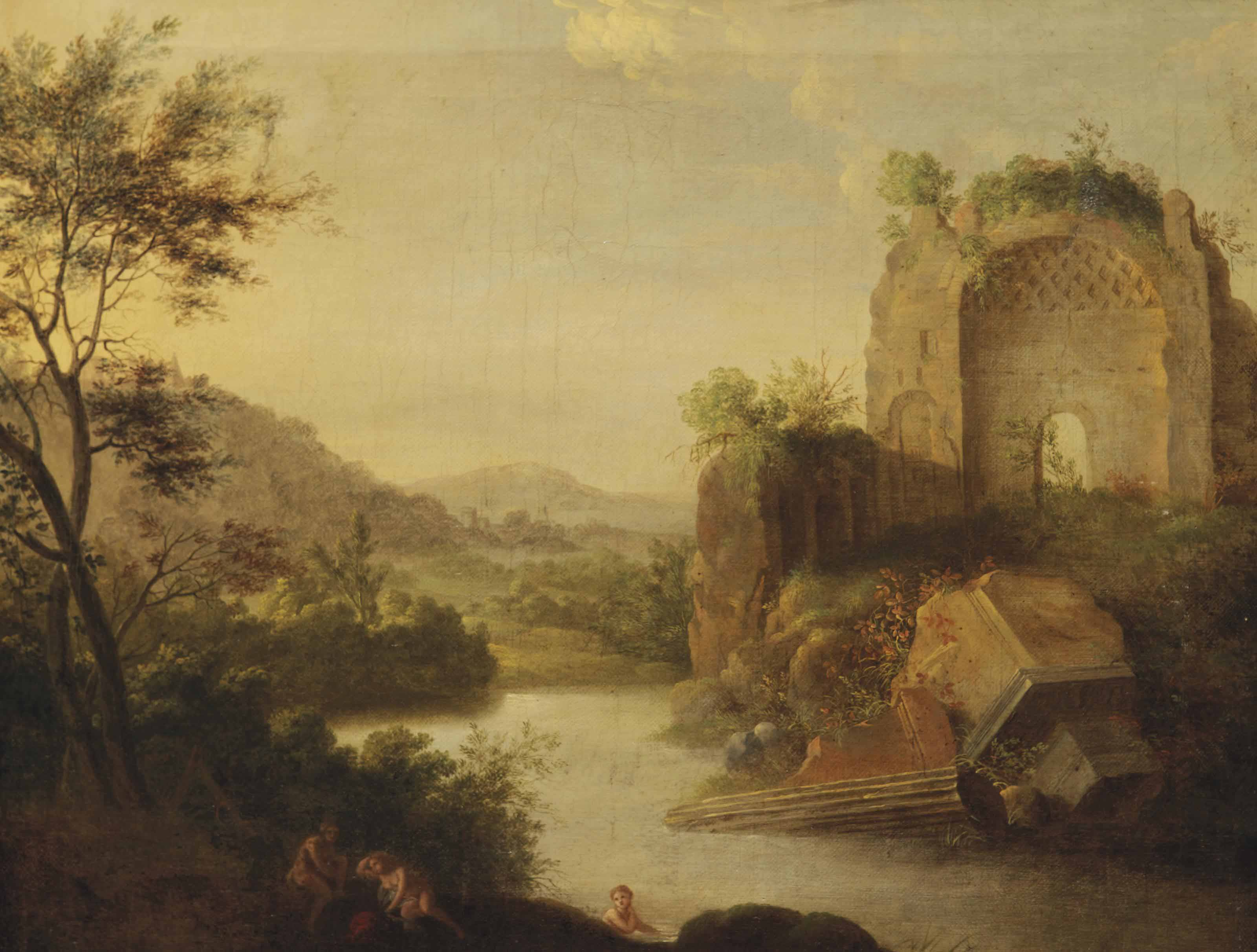 A wooded landscape with bathing nymphs near classical ruins