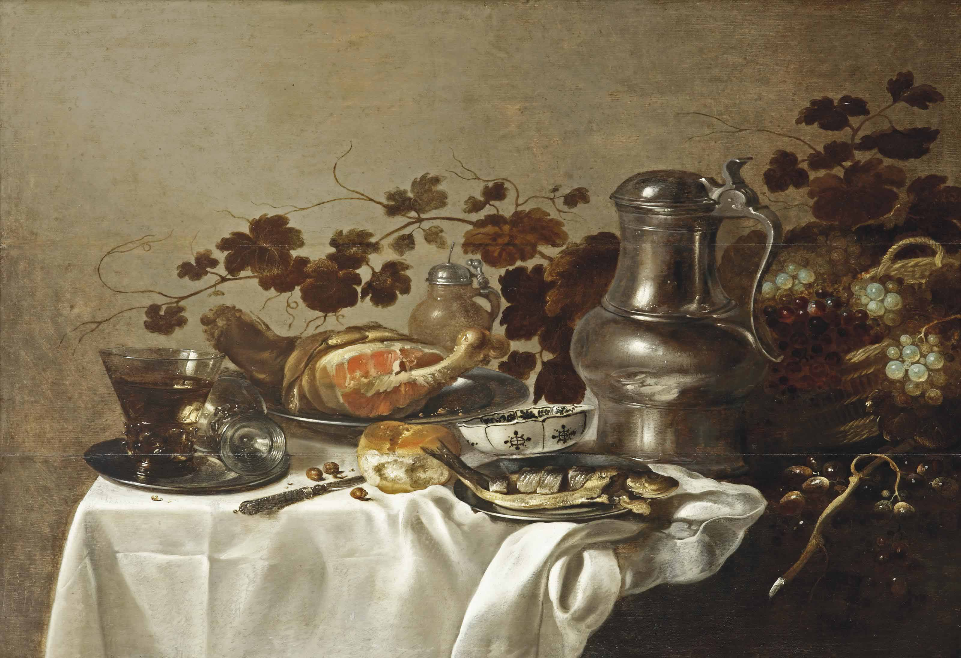 A silver plate with two Roemers, a sliced ham and fish, a 'wan-li' porcelain bowl, bread, a tin jug and wicker basket with grapes and vines, all on a partially draped table