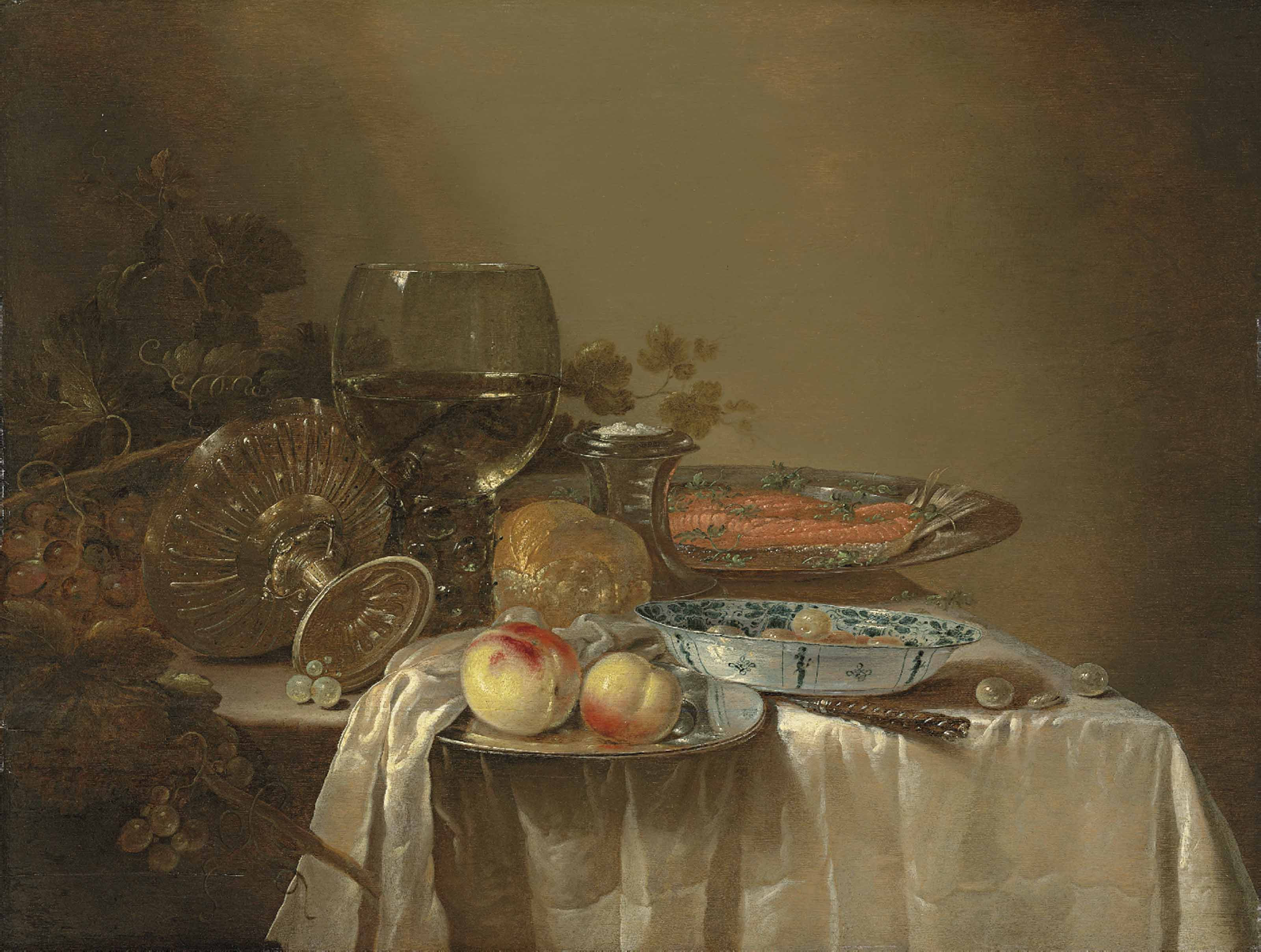 A roemer, an upturned tazza, grapes, peaches and salmon on pewter platters, olives in a porcelain bowl, and other objects on a partly draped table