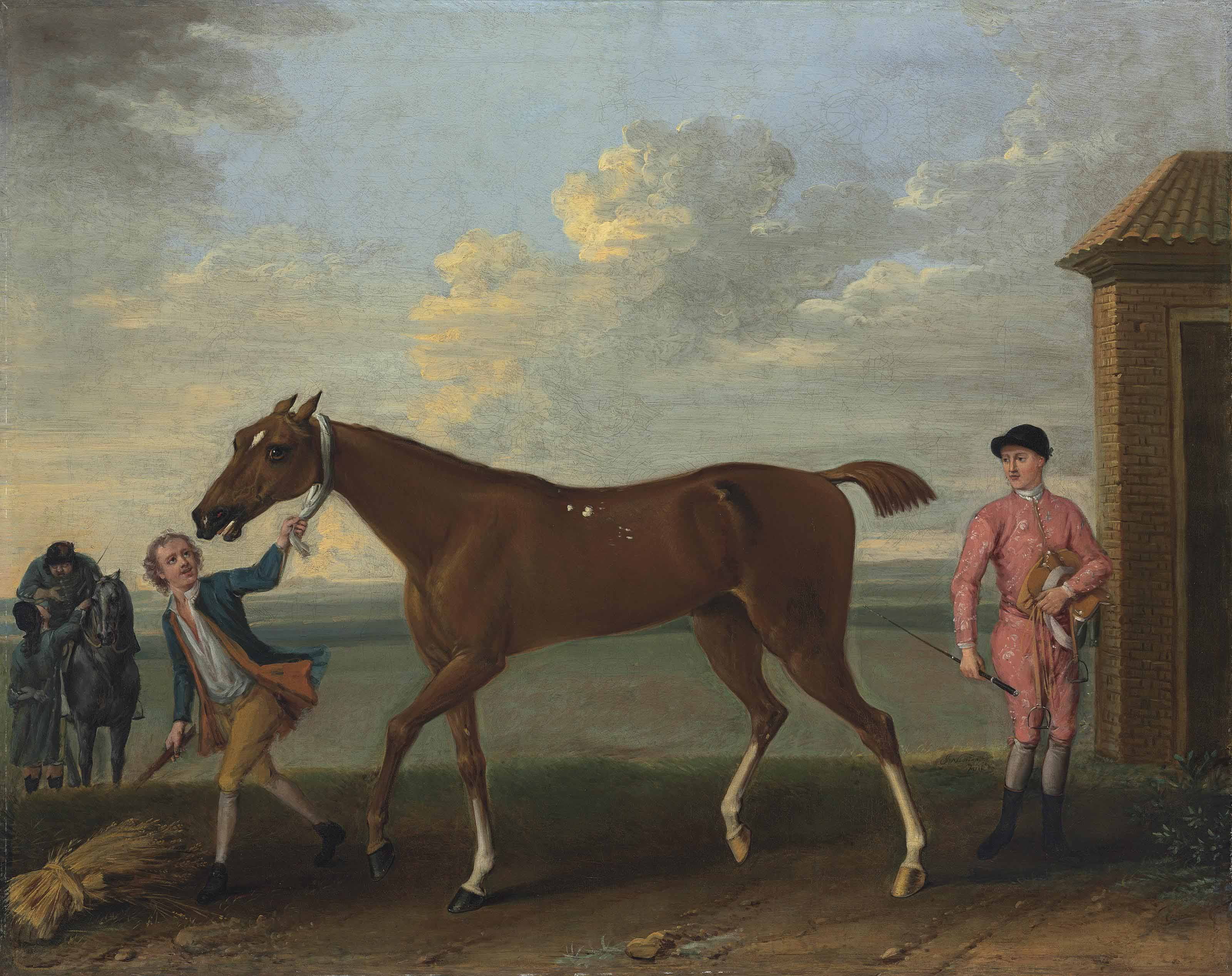 A chestnut racehorse held by a groom, with a jockey dismounted, by the King's Stables, Newmarket