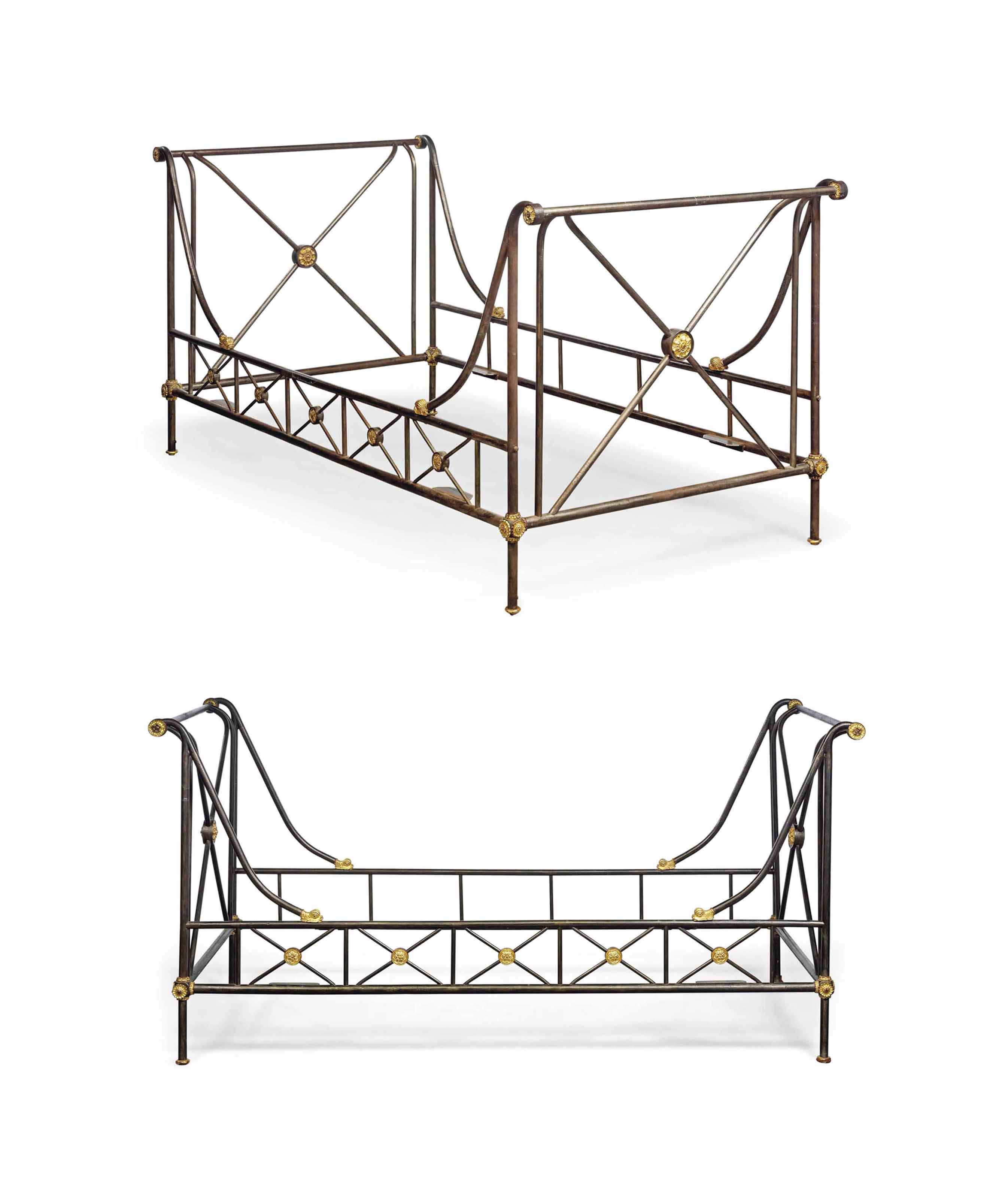 A NEAR PAIR OF EMPIRE STYLE PARCEL-GILT AND PATINATED STEEL BEDS