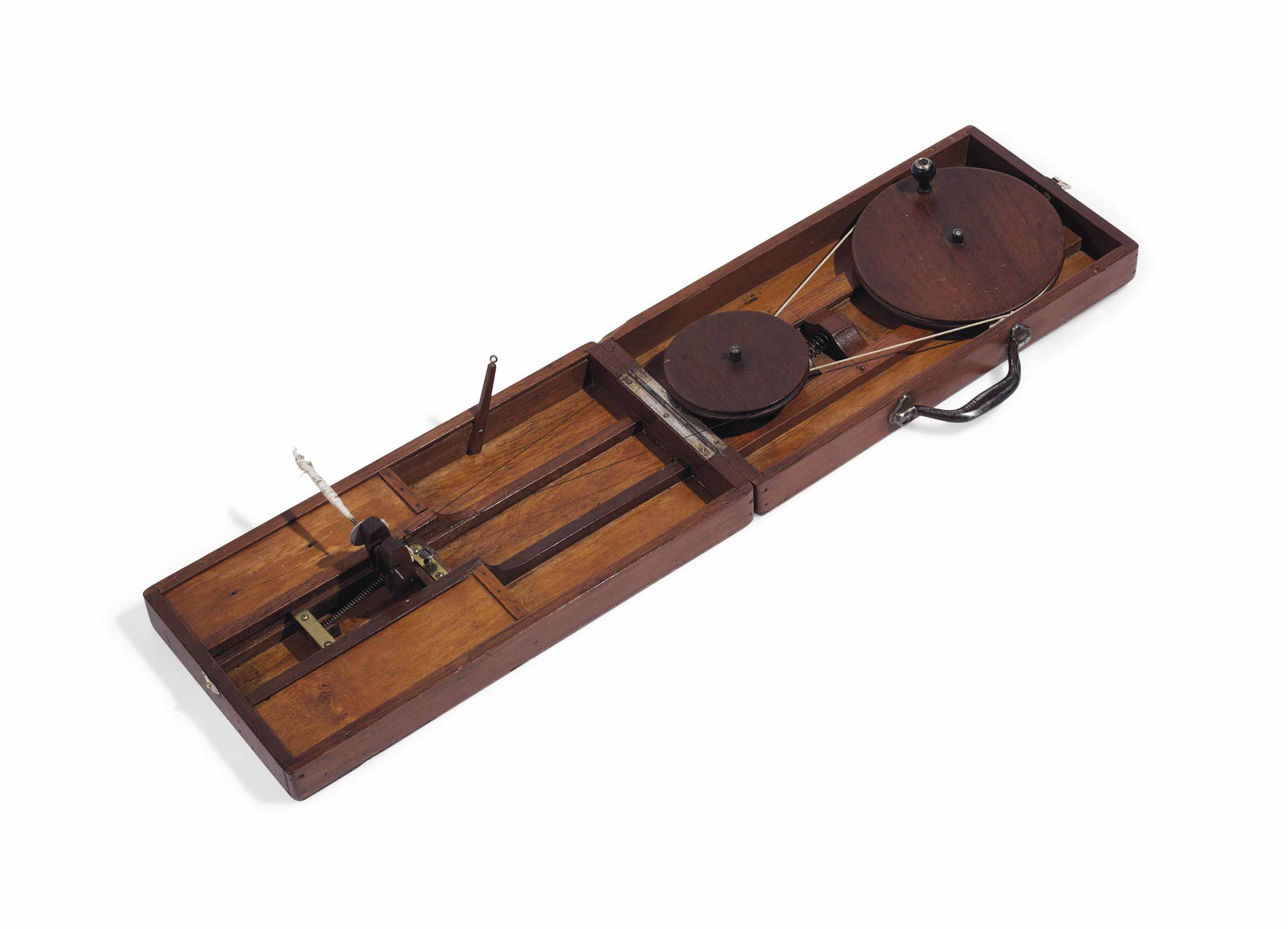 [GANDHI, Mohandas Karamchand (1869-1948)]. A portable charkha (spinning wheel), owned by Gandhi, and reputedly used by him in Yerawda Jail (Pune) in c.1930, Indian teak, hollow metal handle (clasp replaced, strings and thread renewed, signs of use), the folding case approximately 915 x 233 x 40 mm when open.