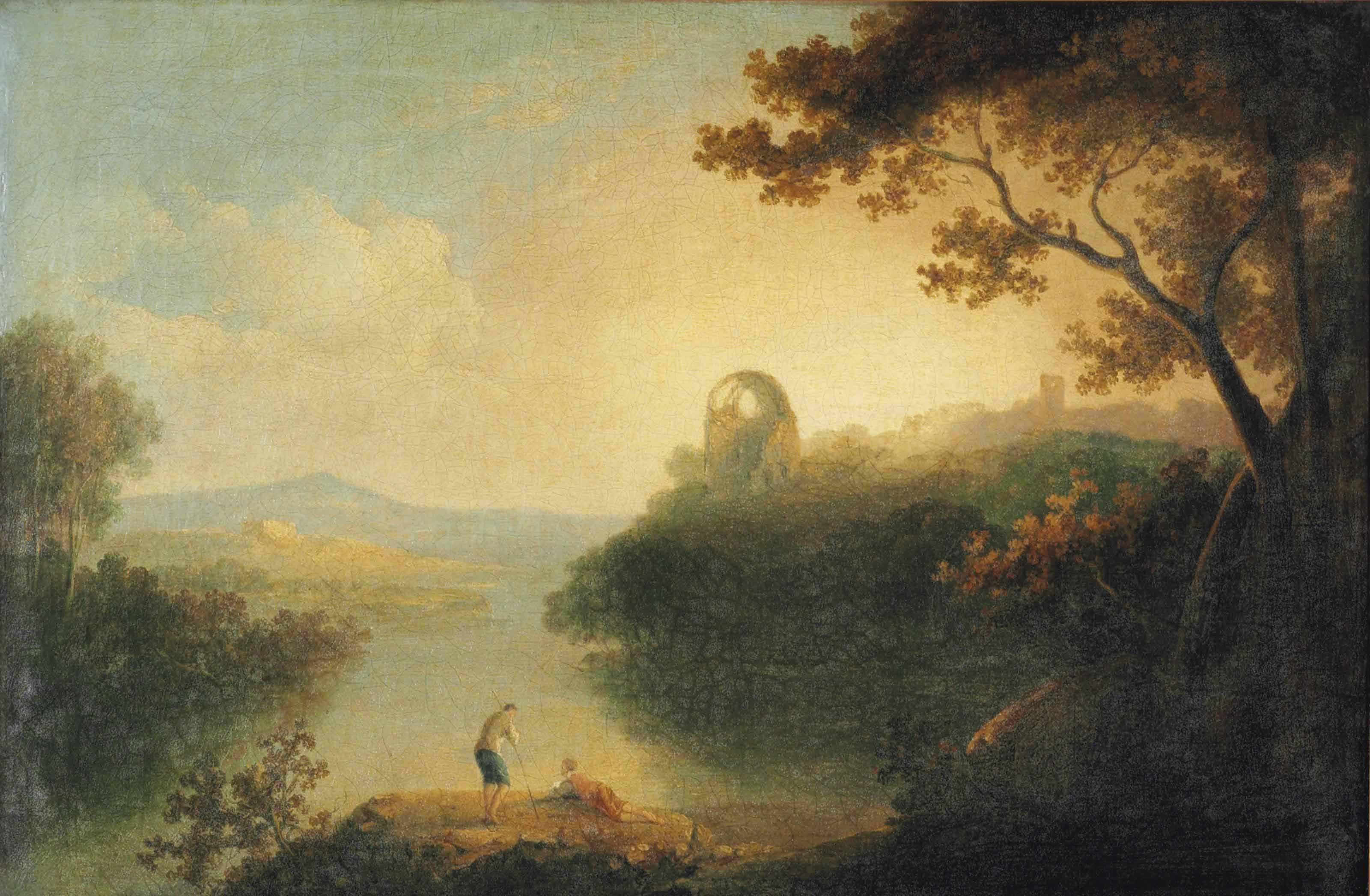 An Italianate river landscape with figures conversing on a bank, ruins beyond