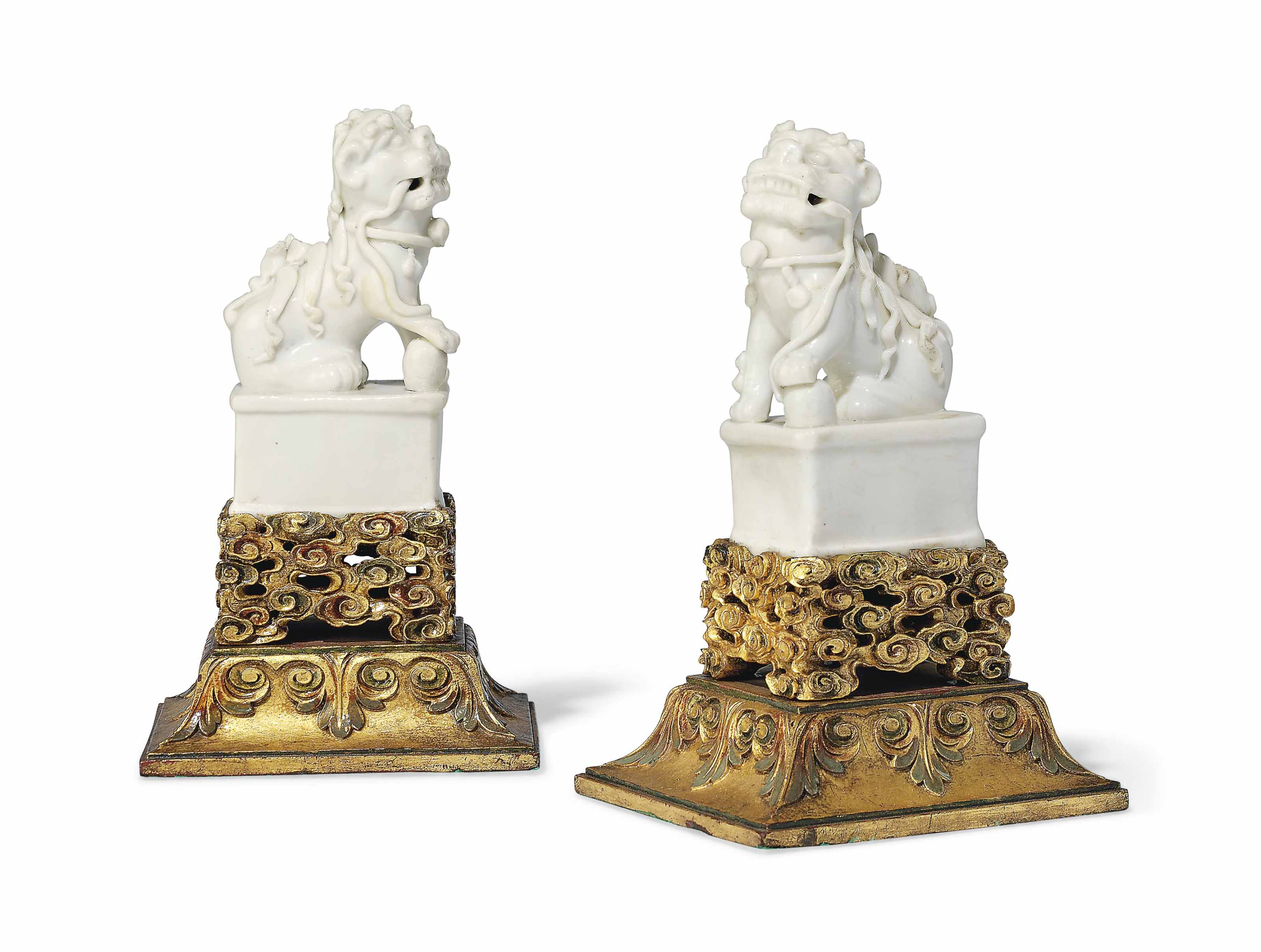 A CHINESE PAIR OF DEHUA BUDDHIST LIONS ON GILT WOOD BASES