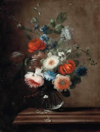Roses, a tulip, corn flowers, a lilly and hollyhocks in a glass vase on a stone ledge