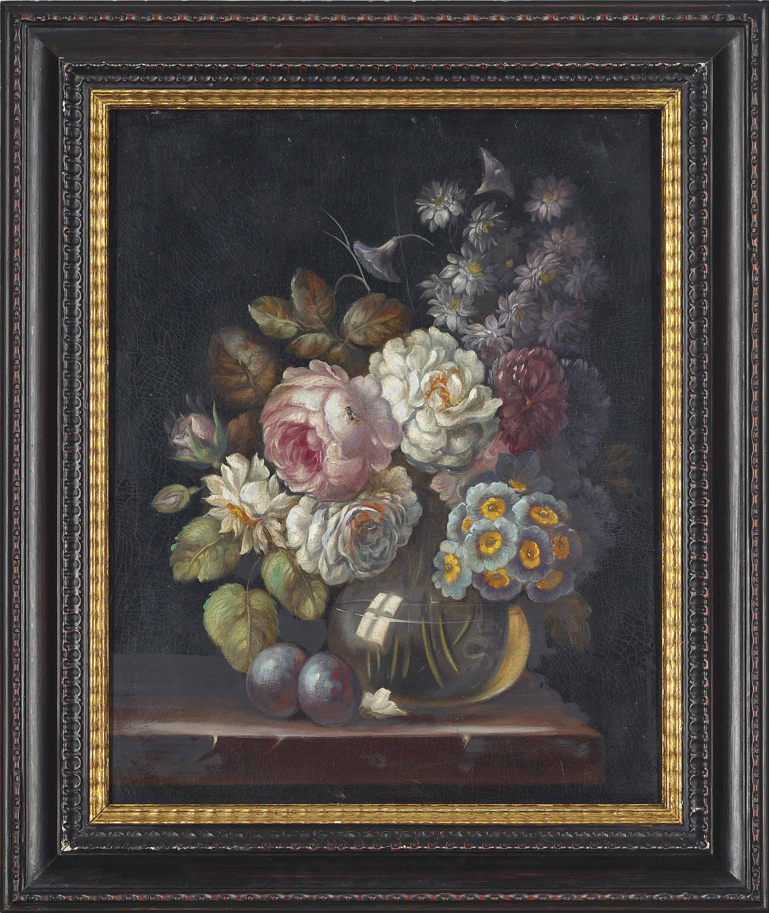 Roses, snowballs and other flowers in a glass vase on a stone ledge