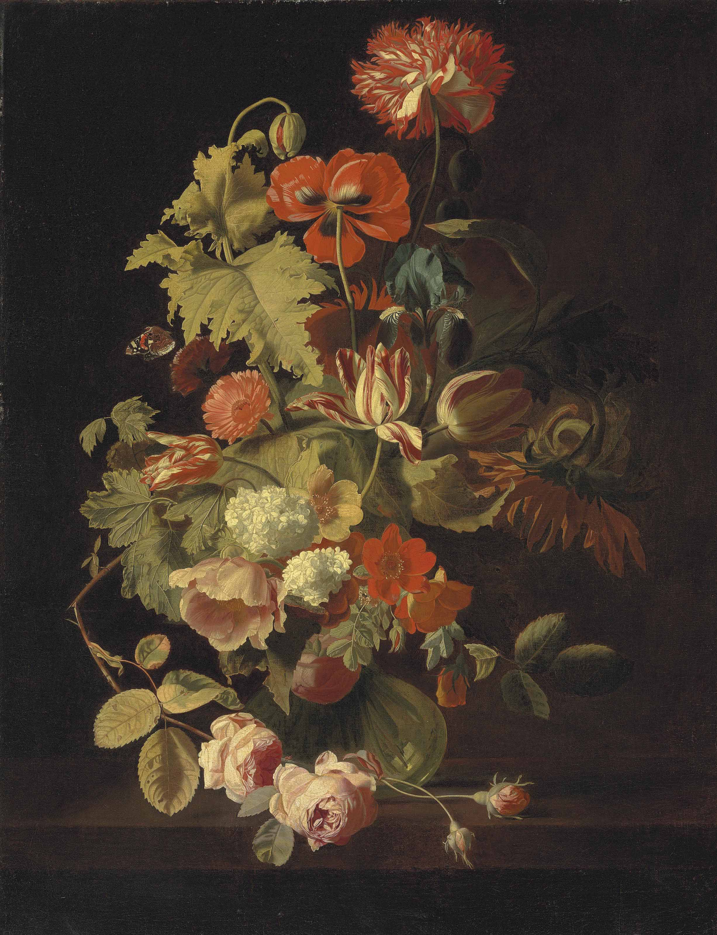 A carnation, iris, roses, tulips and other flowers in a glass vase on a stone ledge