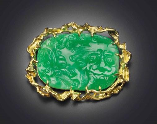 A CARVED MOTTLED GREEN JADEITE