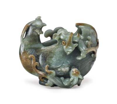 A CHINESE CARVED GREEN AND RUS