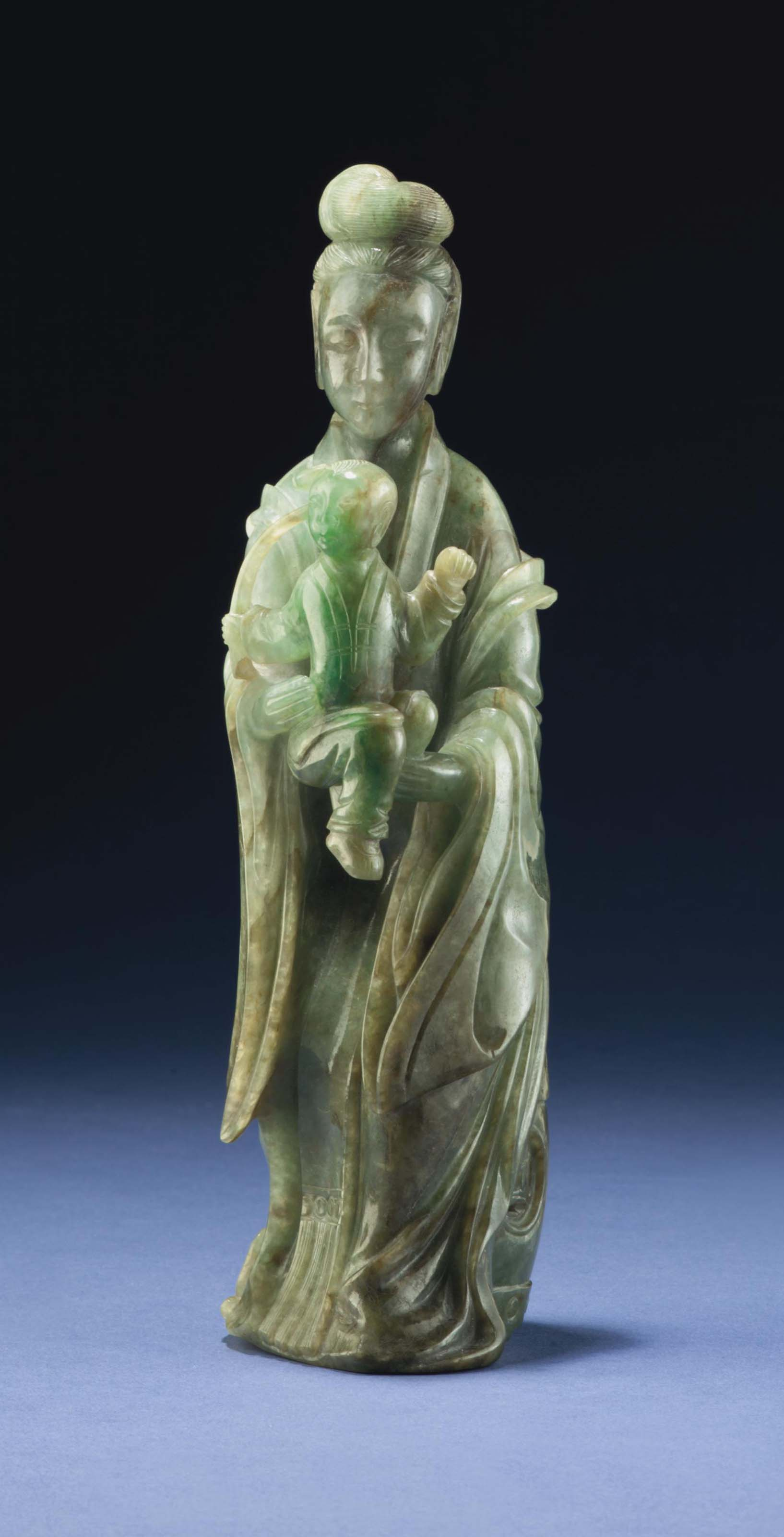 A MOTTLED JADEITE FIGURE OF A