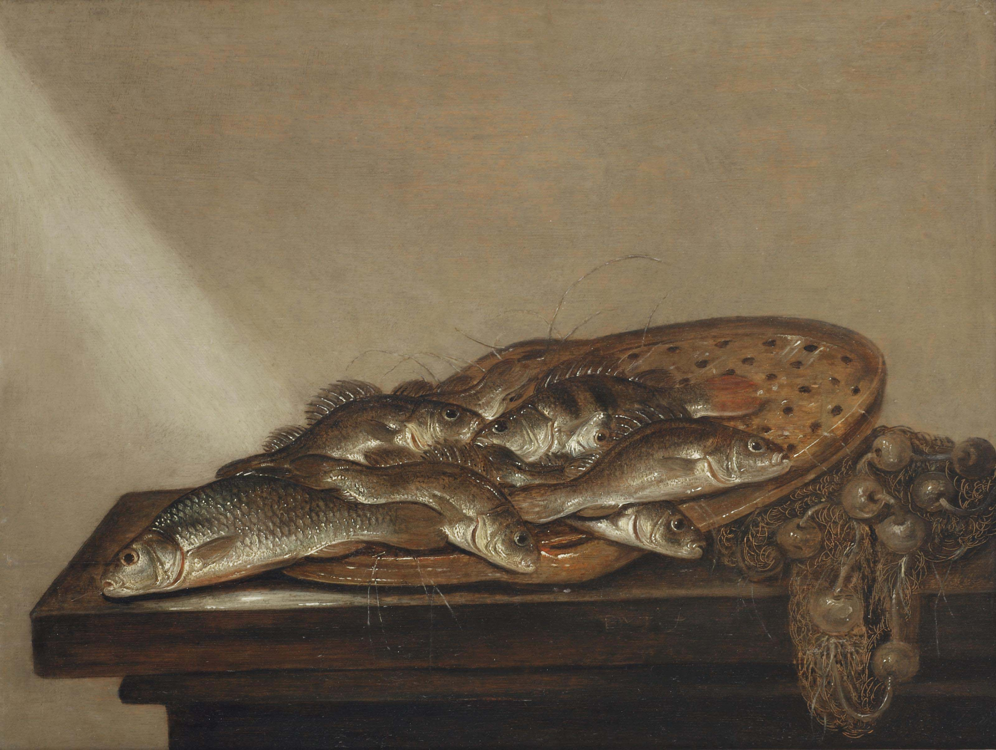 Various fish on a terra-cotta strainer, together with a fishing net on a table