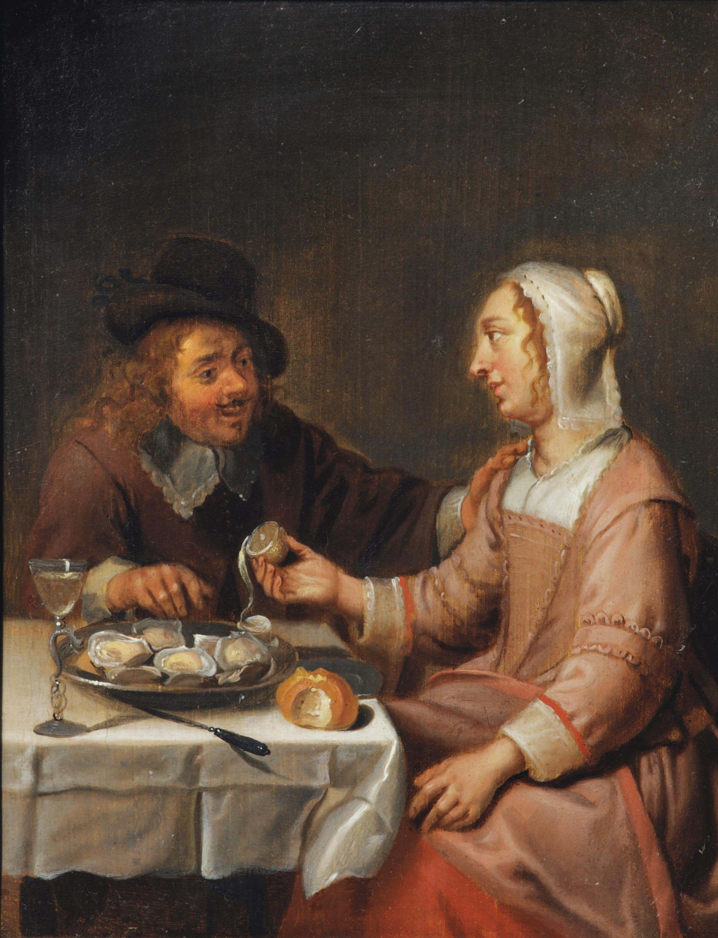 A couple seated at a table, eating oysters