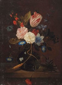 A tulip, a cornflower, roses, a carnation and other flowers in a glass vase on a ledge
