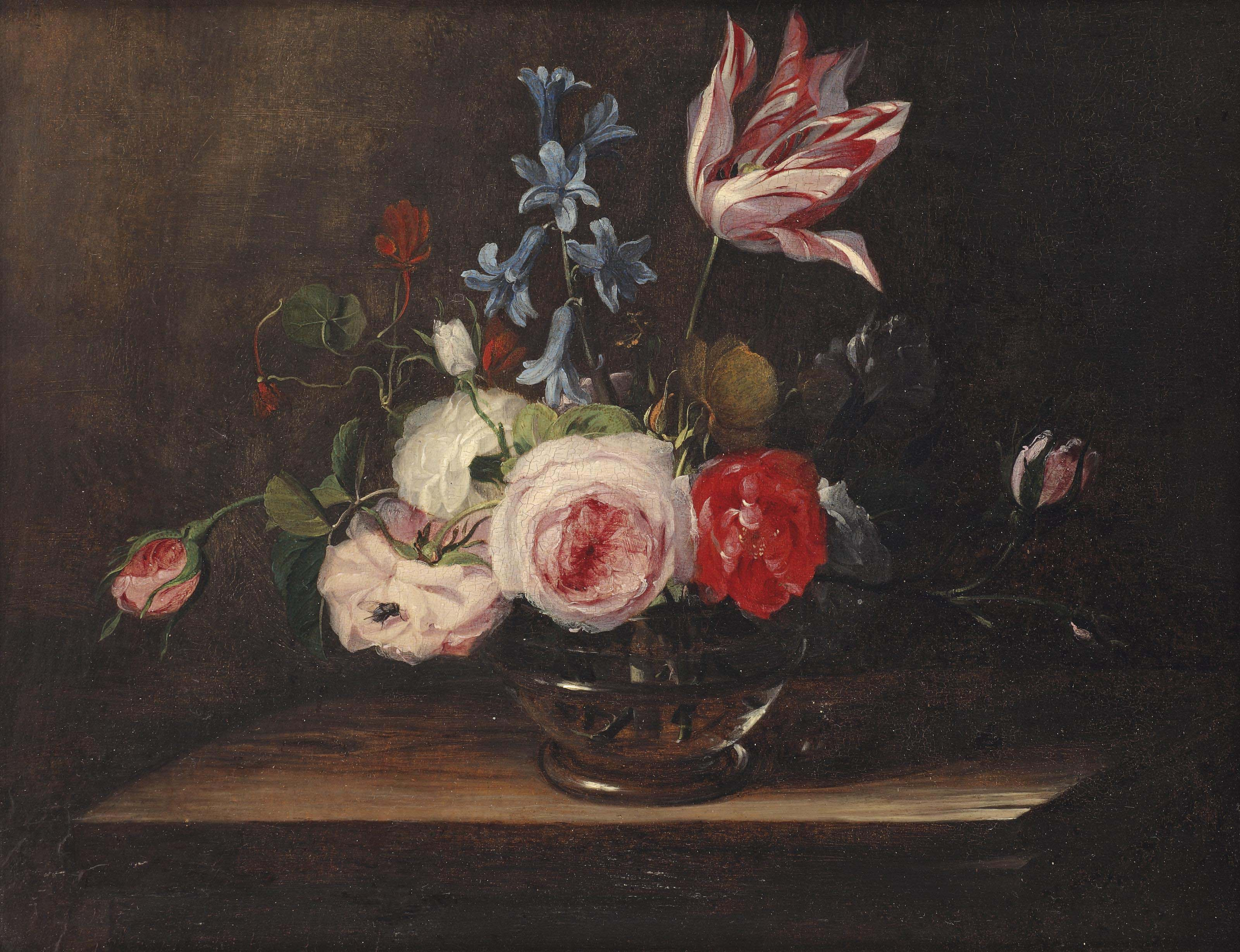 Roses, a tulip, and bluebells in a glass vase, on a wooden ledge