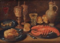 A roasted chicken, lobster, olives, lemons, bread, goblets and a caraffe, all on a wooden ledge