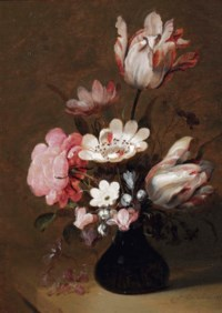 A glass vase with tulips, peonies and other flowers on a stone ledge
