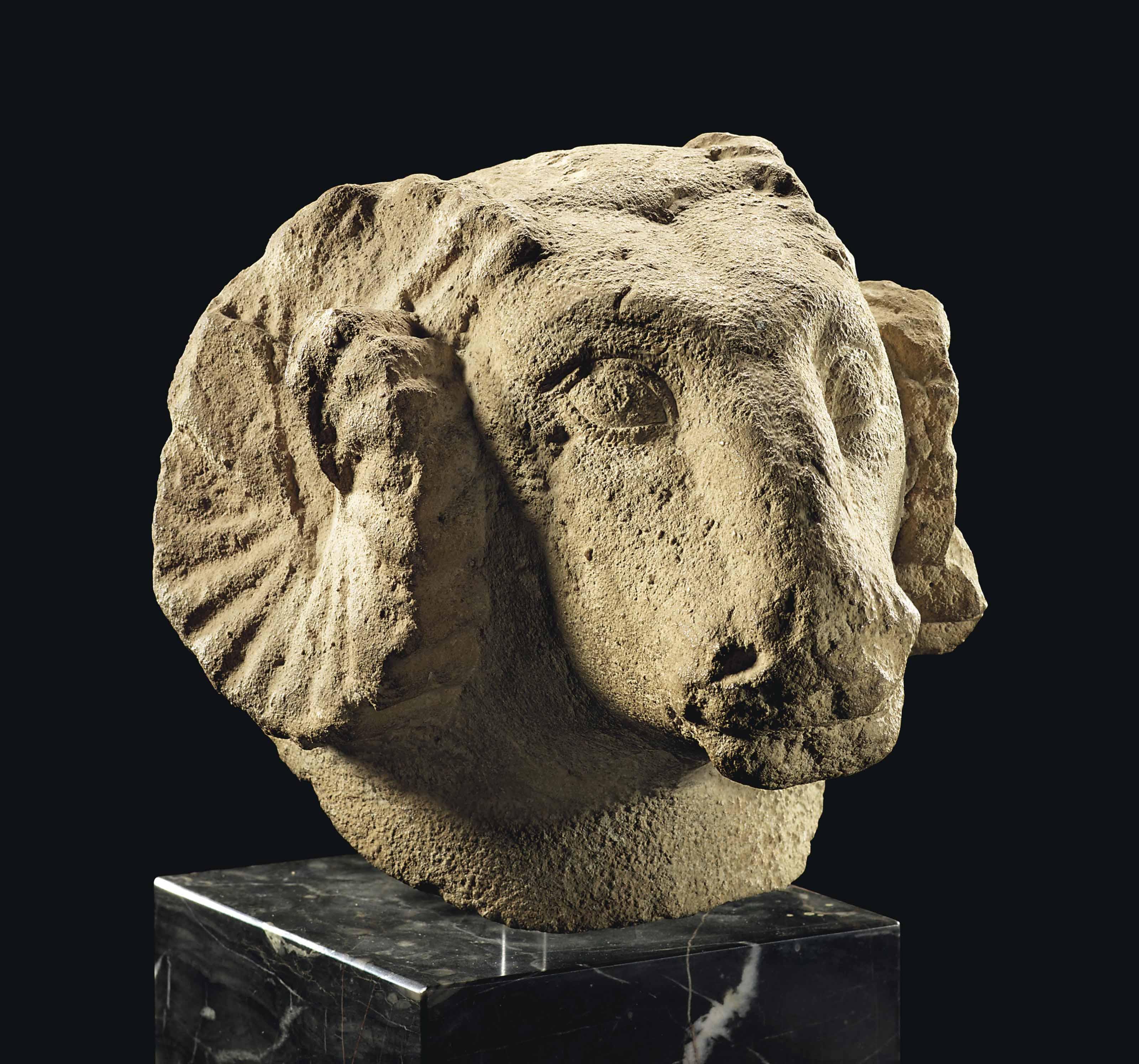 AN EGYPTIAN LIMESTONE RAM'S HEAD