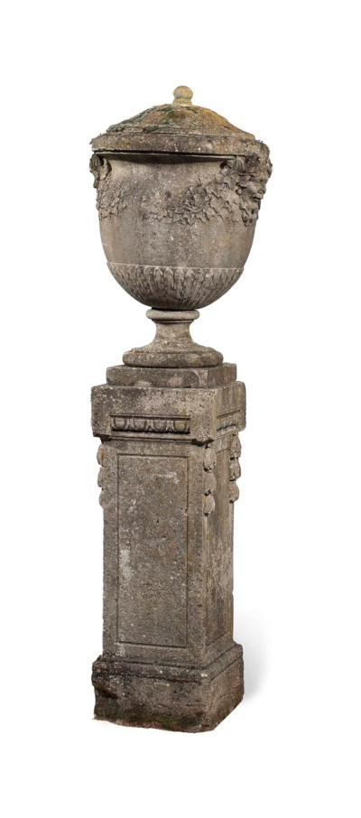 A CARVED STONE URN ON PLINTH