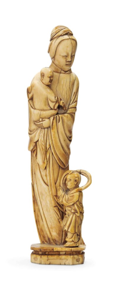 AN IVORY CARVING OF A LADY AND