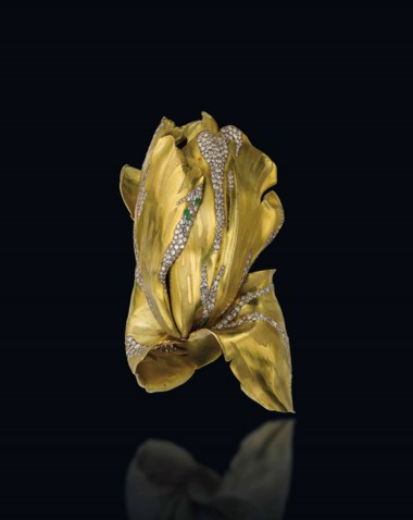 A gold, diamond and green garnet 'Parrot Tulip' bangle, by JAR. Designed as a sculpted gold flower, the two petals at the base forming the hinged cuff, enhanced by single-cut diamonds and circular-cut green garnets, 1994, flower size 9.5 cm, in pink leather fitted JAR case. Sold for CHF 3,525,000 on 11 November 2014 at Christie's in Geneva