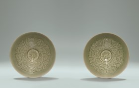 TWO RARE AND SUPERBLY CARVED YAOZHOU CELADON SHALLOW BOWLS