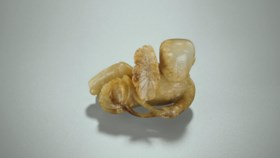 A WHITE AND RUSSET JADE CARVING OF MOHOULUO HOLDING A LOTUS
