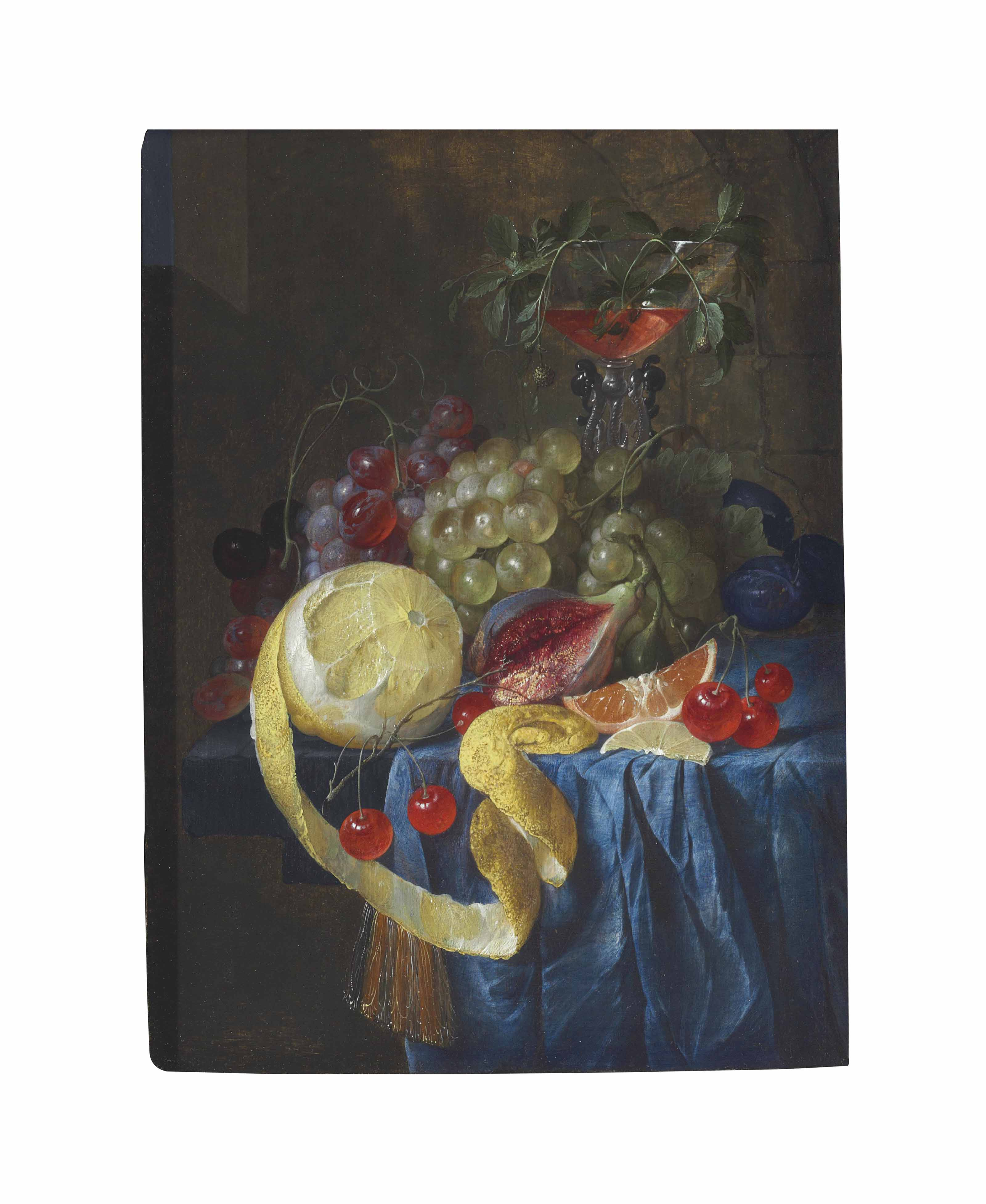 A partly-peeled lemon, fig, slice of orange, cherries, plums and bunches of grapes with a façon de Venise wine glass on a draped stone ledge