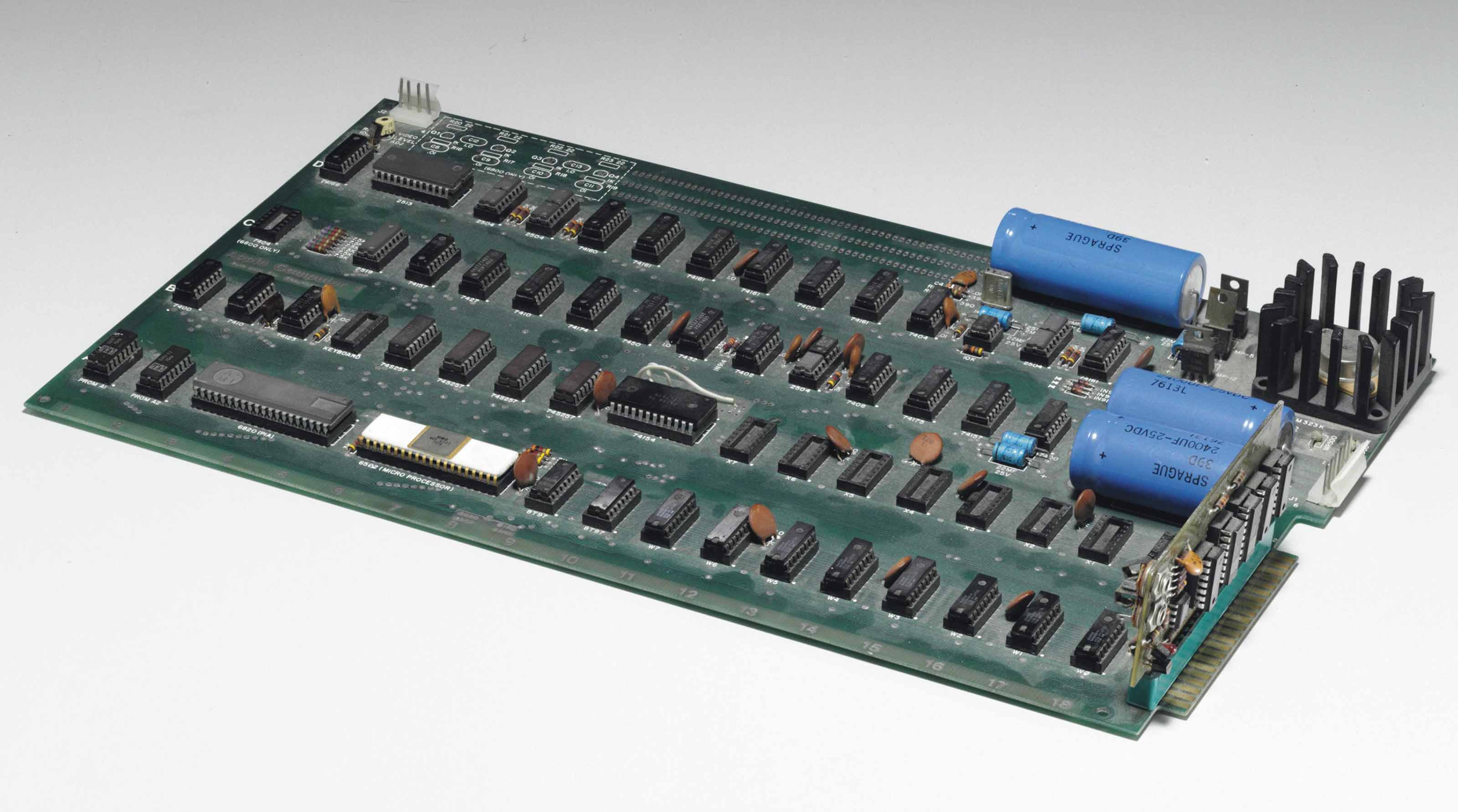 "[COMPUTING]. -- APPLE-1 -- Personal Computer. An Apple-1 motherboard, numbered ""01-0083"" in black ink on the reverse, printed circuit board with 4 rows A-D and columns 1-18, three capacitors, heatsink, cassette board connector, 4K RAM, keyboard interface, firmware in PROMS, low-profile sockets on all integrated circuits, video terminal, wires and electrical tape to reverse. Palo Alto. Ca. Copyright 1976. Provenance: purchased by the current owner, proprietor of a retail computer store in Northern California, in 1978."