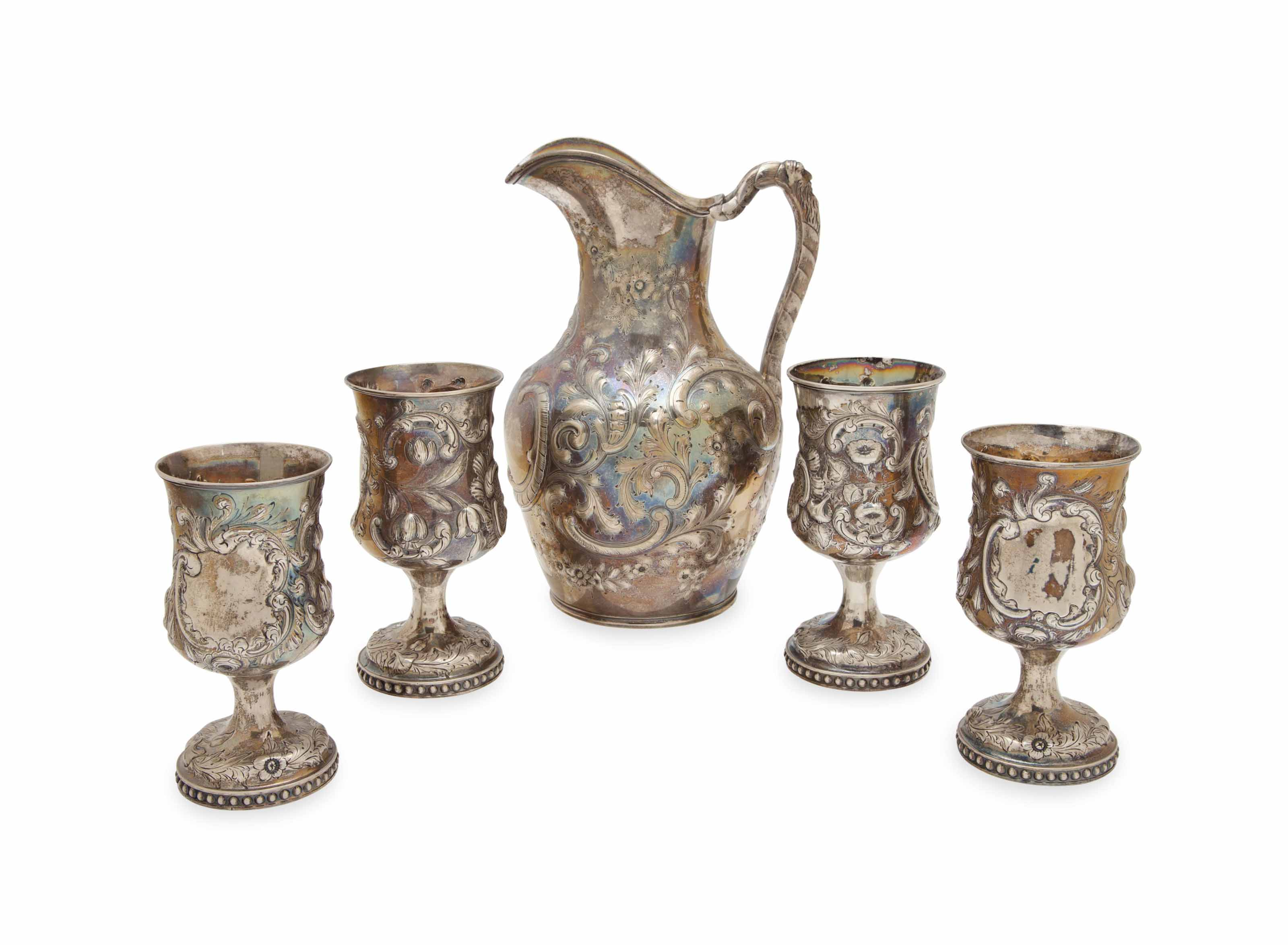 AN EARLY AMERICAN REPOUSSE SILVER WATER PITCHER, AND FOUR GOBLETS,