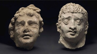 Two stucco heads of youths