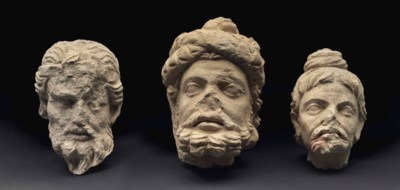 A group of three stucco heads