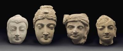 A group of four stucco heads