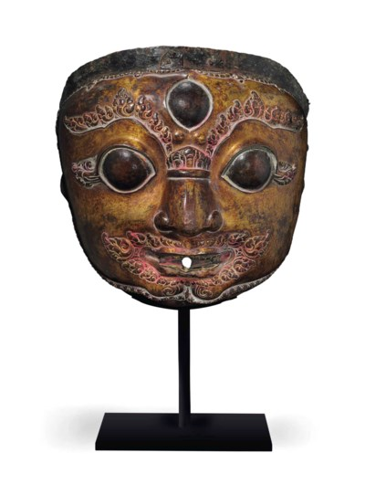A gilt copper repousse mask of