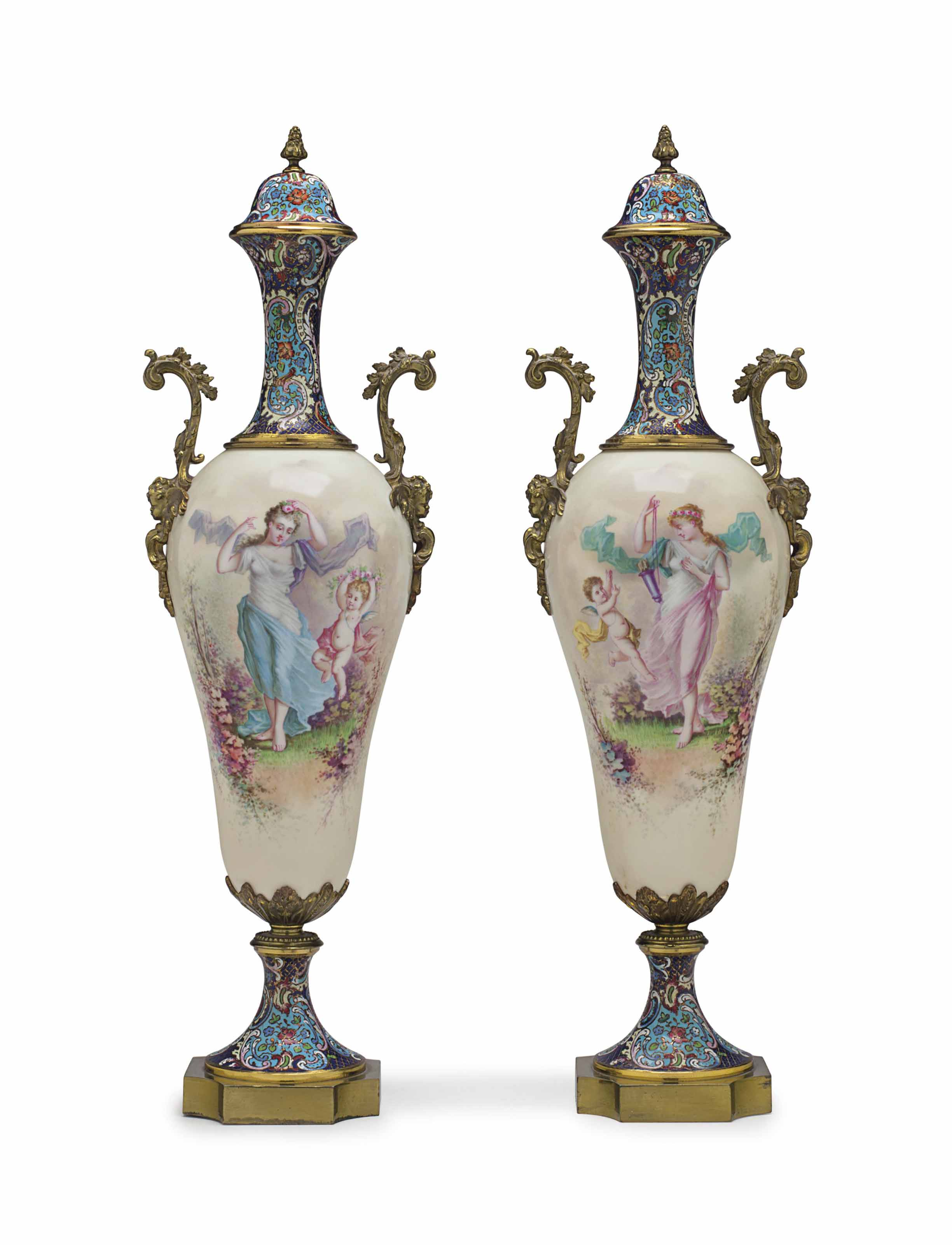 A PAIR OF ORMOLU AND CHAMPLEVE-ENAMEL MOUNTED SEVRES STYLE PORCELAIN VASES AND COVERS